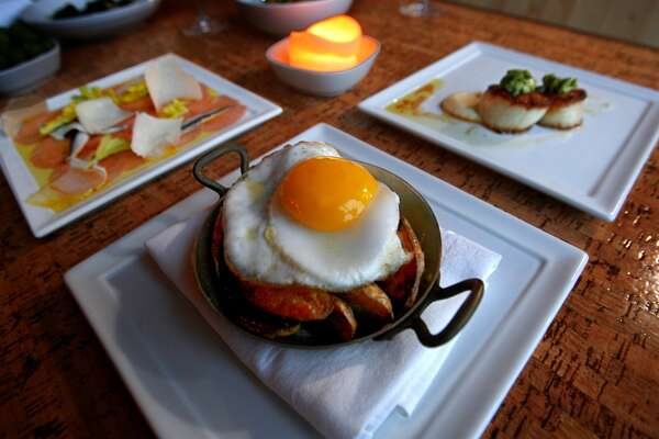 "How to Cook a Wolf   : This Ethan Stowell restaurant serves Italian-inspired small plates that are ""uncomplicated and rustic."" 2208 Queen Anne Ave N., Queen Anne.   Pictured are roasted fingerling potatoes with a fried duck egg (foreground), veal carpaccio (left) and seared sea scallop (right)."