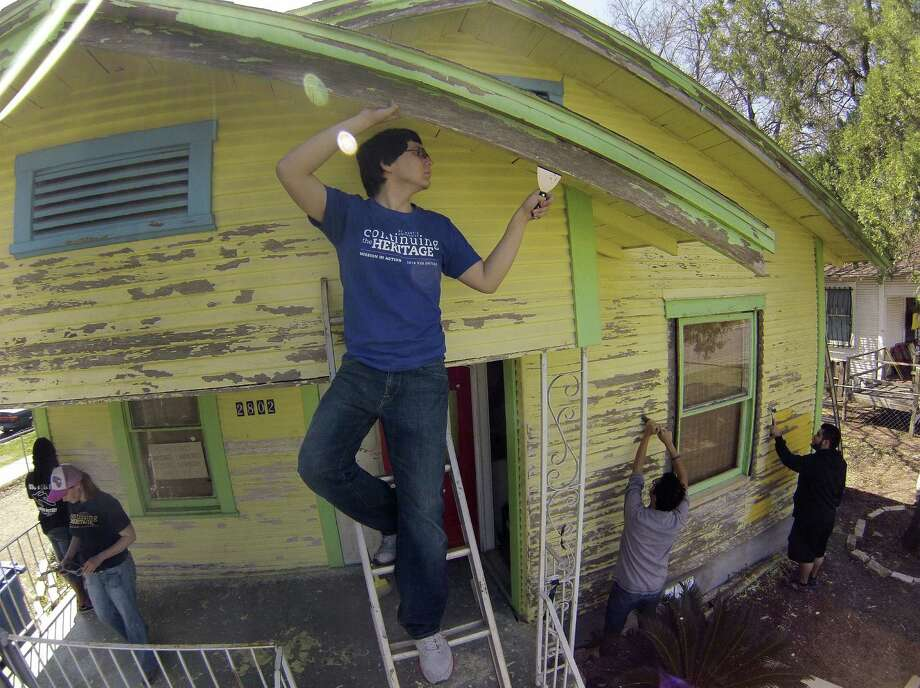 """Jonathan Vela helps scrape the exterior of the House of Teens after-school center on the West Side. """"I love doing service,"""" he said, adding, """"it's inspiring."""" The center for sixth-graders through 12th-graders is run by Divine Redeemer Presbyterian Church. Photo: Photos By Billy Calzada / San Antonio Express-News / San Antonio Express-News"""