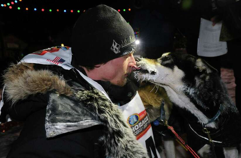 Dallas Seavey gets some love from one of his dogs after winning the 2014 Iditarod Trail Sled Dog Rac