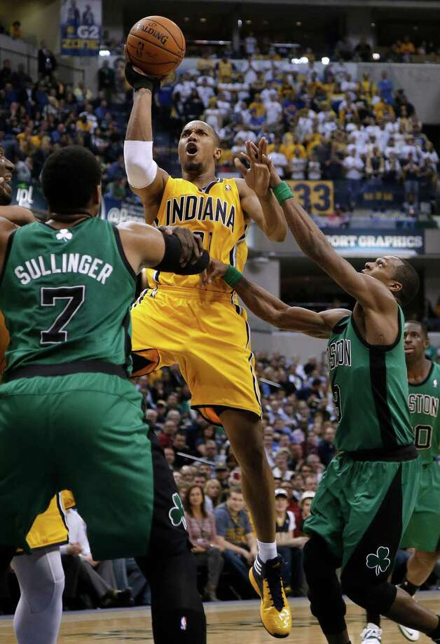 Indiana Pacers forward David West, center, is fouled by Boston Celtics guard Rajon Rondo, right, while shooting over Celtics' Jared Sullinger during the second half of an NBA basketball game in Indianapolis, Tuesday, March 11, 2014. The Pacers won 94-83. (AP Photo/AJ Mast) ORG XMIT: INAM107 Photo: AJ MAST / FR123854 AP