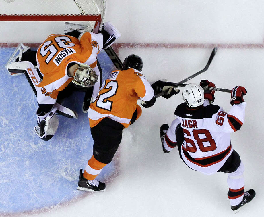 New Jersey Devils' Jaromir Jagr (68), of the Czech Republic, scores a goal past Philadelphia Flyers' Mark Streit (32), of Switzerland, and Steve Mason (35) during the third period of an NHL hockey game, Tuesday, March 11, 2014, in Philadelphia. New Jersey won 2-1. (AP Photo/Matt Slocum) ORG XMIT: PXC110 Photo: Matt Slocum / AP
