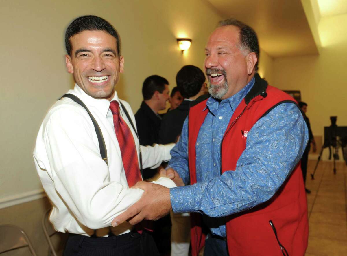 Nicholas LaHood, left, who is running in the Democratic primary for the district attorney nomination, is greeted by Art Silva at San Antonio Professional Firefighters Banquet Hall on election night, Tuesday, March 4, 2014.