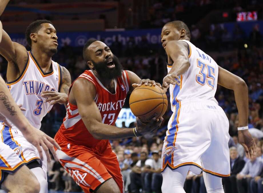 Rockets shooting guard James Harden drives between two Thunder defenders. Photo: Sue Ogrocki, Associated Press