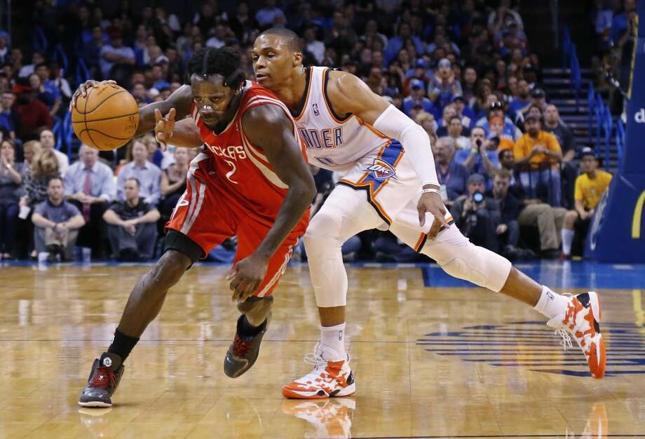 Thunder point guard Russell Westbrook tries to poke the ball away from Pat Beverley of the Rockets. Photo: Sue Ogrocki, Associated Press