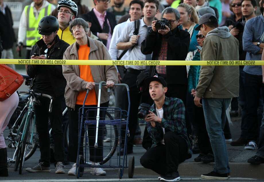 Bystanders watch from down the street as a five alarm blaze of a partially completed apartment complex burns March 11, 2014 at 4th St. and Long Bridge Vara in San Francisco. Photo: Leah Millis, The Chronicle