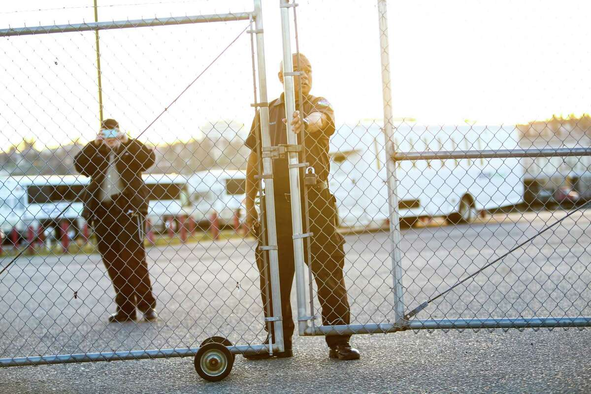 A worker shuts a gate at the privately-run Tacoma Northwest Detention Center which houses U.S. Immigration and Customs Enforcement detainees. A group of detainees in the facility are on the fifth day of a hunger strike. Family members and supporters have been gathering outside the facility to call for immigration reform and better treatment of the detainees. Photographed on Tuesday, March 11, 2014.