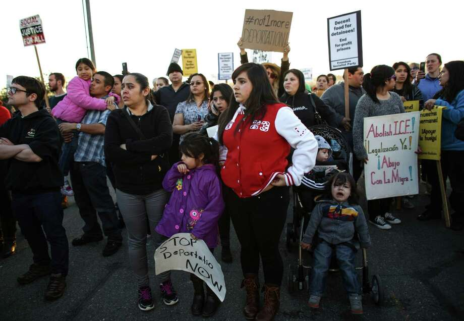 Family members watch as a bus is moved at the privately-run Tacoma Northwest Detention Center which houses U.S. Immigration and Customs Enforcement detainees. A group of detainees in the facility are on the fifth day of a hunger strike. Family members and supporters have been gathering outside the facility to call for immigration reform and better treatment of the detainees. Photographed on Tuesday, March 11, 2014. Photo: JOSHUA TRUJILLO, SEATTLEPI.COM / SEATTLEPI.COM