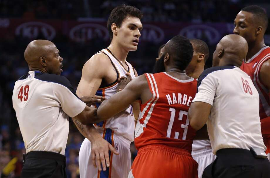 Rockets shooting guard James Harden has to be separated from Steven Adams of the Thunder. Photo: Sue Ogrocki, Associated Press