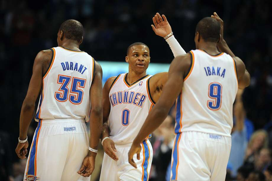 Russell Westbrook (center) gets some love from Thunder teammate Serge Ibaka during the 106-98 win over Houston. Photo: Mark D. Smith, Reuters