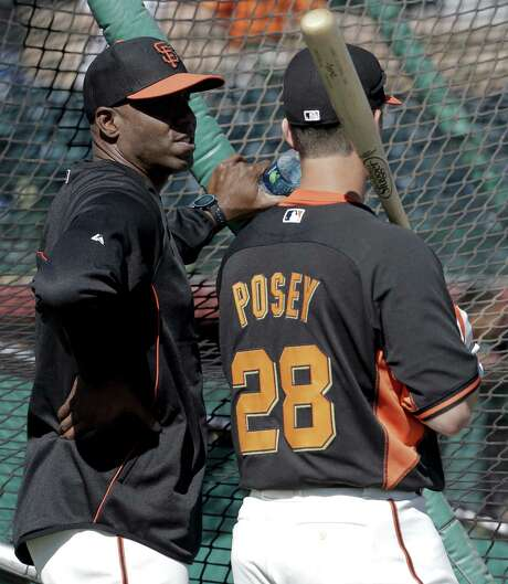Former Giants great Barry Bonds (left) oversees a recent spring training hitting session with catcher Buster Posey. Photo: Chris Carlson / Associated Press / AP