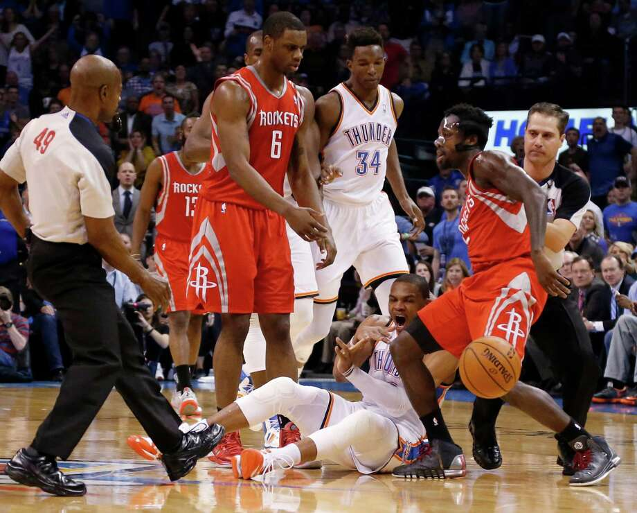 It didn't take long for Rockets guard Pat Beverley, right, to again get under the skin of the Thunder's Russell Westbrook, bottom, who reacts to a first-quarter foul by Beverley. It was their first meeting since locking horns (and knees) in last year's playoffs. Photo: Sue Ogrocki, STF / AP