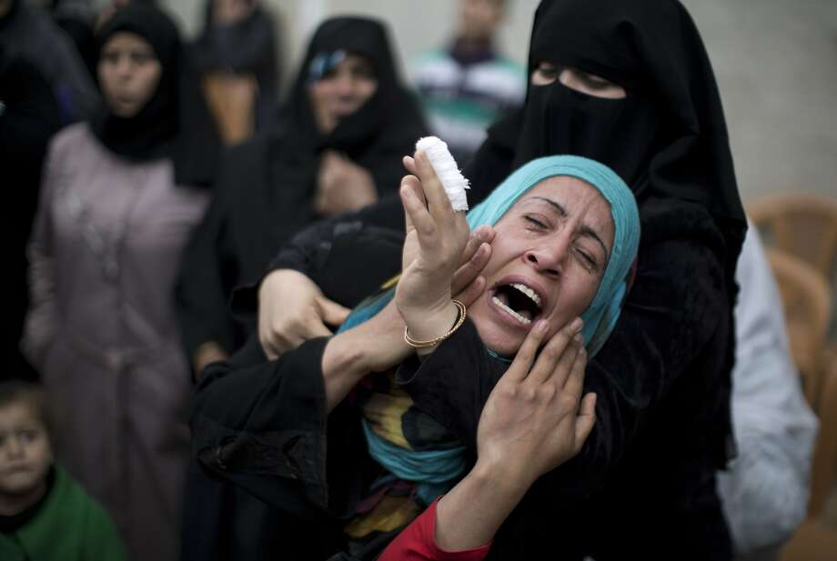 A relative of  Shaher Abu Shanab, one of three Palestinian militants from the Islamic Jihad's armed wing, the Al-Quds Brigades who were killed in an Israeli airstrike, mourns during his funeral in Khan Yunis in the southern Gaza Strip, on March 11, 2014. The Israeli army confirmed the strike, saying the air force had targeted Islamic Jihad militants who had fired at troops.  TOPSHOTS/AFP PHOTO / MAHMUD HAMSMAHMUD HAMS/AFP/Getty Images Photo: Mahmud Hams, AFP/Getty Images