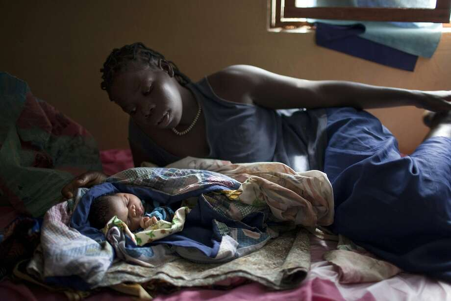 Rose Elia, 23, rests together with her new-born baby after giving birth  in a ward of the public hospital of Yambio, in the south of South Sudan, on March 11, 2014. A team of Medecins Sans Frontieres (MSF, doctors without borders) helps the staff of the hospital in order to reduce the rate of maternal mortality, the highest in the country. As ongoing fighting in South Sudan shatters any pretense of a ceasefire between government troops and rebels, analysts fear the conflict could engulf the region, as former foes fight old wars in a new country.    TOPSHOTS/AFP PHOTO / JM LOPEZJM LOPEZ/AFP/Getty Images Photo: Jm Lopez, AFP/Getty Images