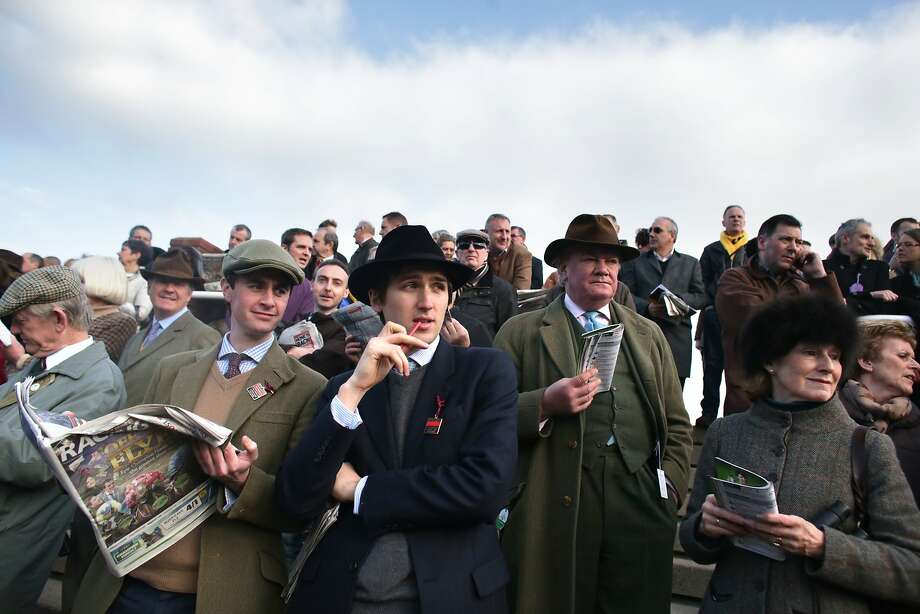 CHELTENHAM, ENGLAND - MARCH 11:  Racegoers look at horses outside the weighing room on the first day of the Cheltenham Festival on March 11, 2014 in Cheltenham, England. Thousands of racing enthusiasts are expected at the four-day festival, which starts today with the festival's Champion Day and is seen as many as the highlight of the jump racing calendar.  (Photo by Matt Cardy/Getty Images) *** BESTPIX *** Photo: Matt Cardy, Getty Images
