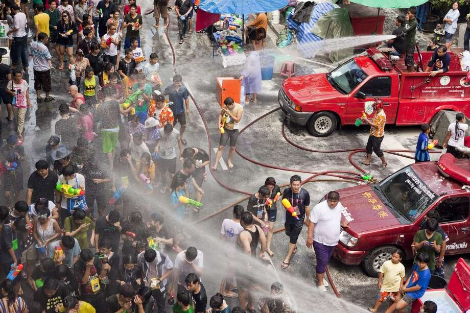 Songkran Water Festival Thai fire fighters soak the crowd with their fire hoses during a community water fight on Silom Road as part of the Songkran Water Festival on April 14, 2013 in Bangkok, Thailand. Though it's definitely a time for fun, Songkran is also traditionally a time to visit and pay respect to elders and pray at the Buddhist monastery. Photo: Jack Kurtz, Getty Images
