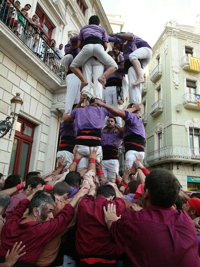 Human Tower Building  The human towers can stand up to 10 levels high, with each layer standing on the shoulders of the people below. The castellers also train to safely dismantle the tower. Photo: Passion Leica, Flickr