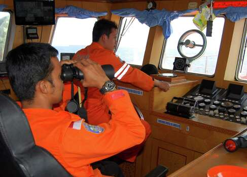 Indonesian National Search and Rescue Agency officials scan the horizon for signs of the missing Malaysia Airlines Boeing 777 on Wednesday, March 12, 2014, in the Strait of Malacca off Sumatra, Indonesia. Malaysia asked India to join the expanding search for the missing Boeing 777 near the Andaman Sea, far to the northwest of its last reported position and a further sign Wednesday that authorities have no idea where the plane might be more than four days after it vanished. Photo: Heri Juanda, AP / AP