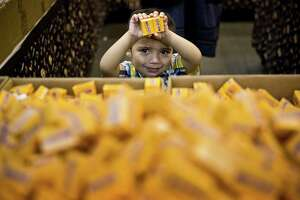 Luke Shaffer, 2, picks Milk Duds candy to watch the Houston Rodeo, Tuesday, March 11, 2014, at Reliant Stadium.