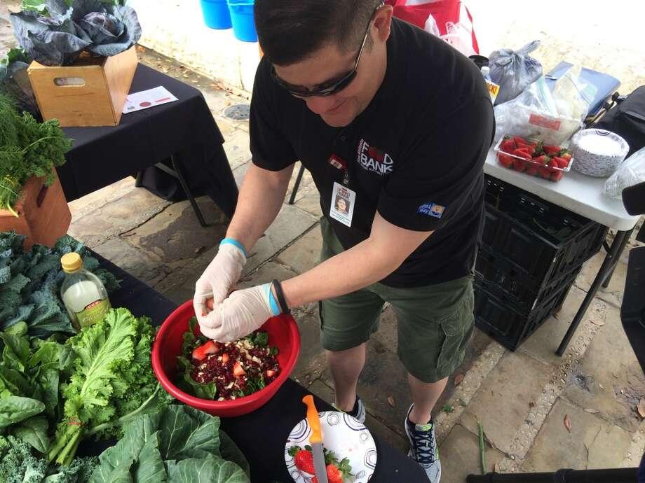 John Velasquez, a nutritionist with the San Antonio Food Bank, makes a salad at the Main Plaza farmers market. Photo: Benjamin Olivo, MySA.com