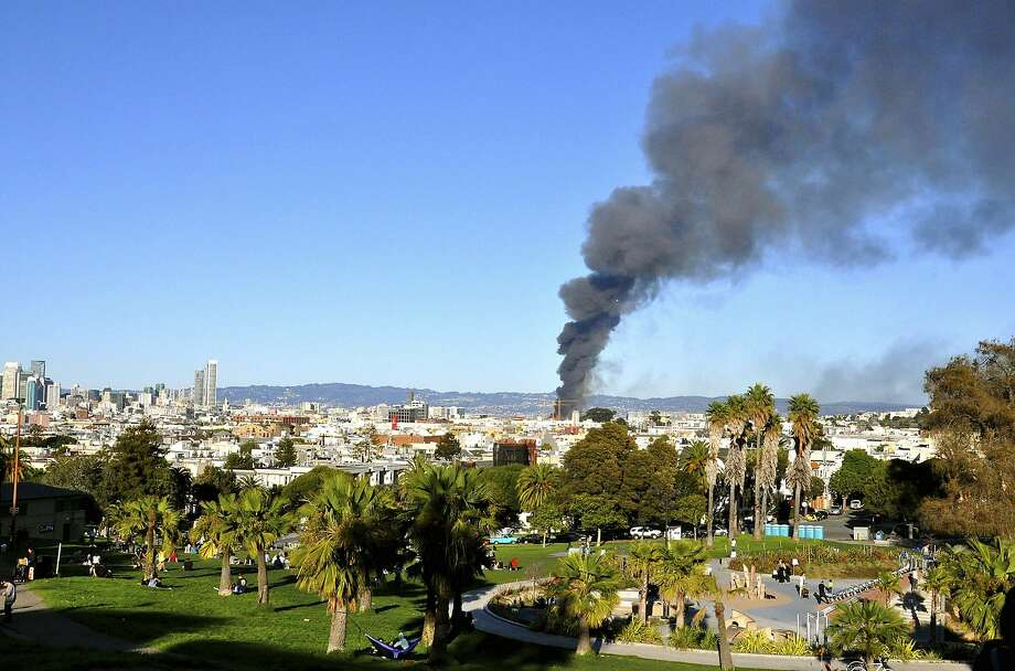 Smoke rises from a fire as seen from Dolores Park in San Francisco, Tuesday. SanFrancisco firefighters prevented a major blaze from spreading from a condominium construction site to nearby buildings. The five-alarm fire started burning at around 5 p.m. on Tuesday in the city's Mission Bay neighborhood, a onetime industrial area that lies along the SanFrancisco Bay. Photo: Danielle Gasbarro, Associated Press