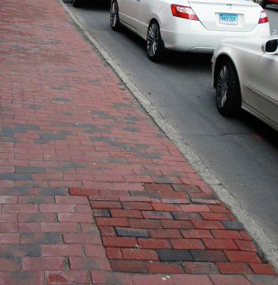 The Westport Downtown Merchants Association paid to have trees removed along Main Street last year, replacing the empty spots with new brick, foreground. Donated trees will facilitate replacement of some of those trees this spring, officials were told Wednesday. Photo: File Photo / Westport News