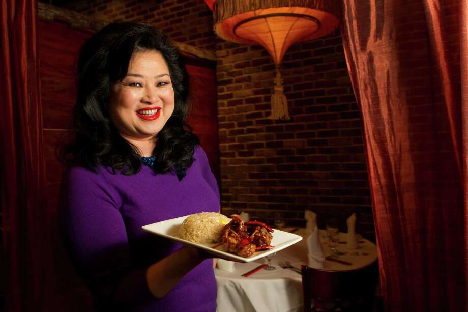 Gigi Huang poses for a photo holding a dish of Orange Beef Tuesday, March 6, 2012, in Houston. This is a dish that her father had on his menu for years before it closed. When she opened her restaurant in the Galleria, it was not on the menu, but her father's loyal customers insisted she serve it. It is now on the menu during lunch only. ( Brett Coomer / Houston Chronicle ) Photo: Brett Coomer, Houston Chronicle / © 2012 Houston Chronicle