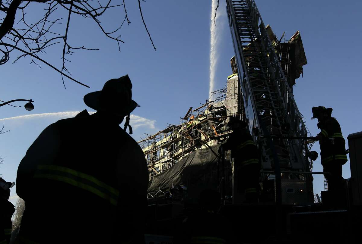 Firefighters continue to pour water on hotspots in San Francisco, Calif. on Wednesday, March 12, 2014, that continue to burn after Tuesday's huge five-alarm fire at a Mission Bay apartment building construction site.