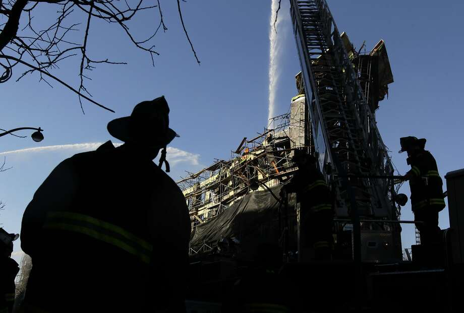 Firefighters continue to pour water on hotspots in San Francisco, Calif. on Wednesday, March 12, 2014, that continue to burn after Tuesday's huge five-alarm fire at a Mission Bay apartment building construction site. Photo: Paul Chinn, The Chronicle