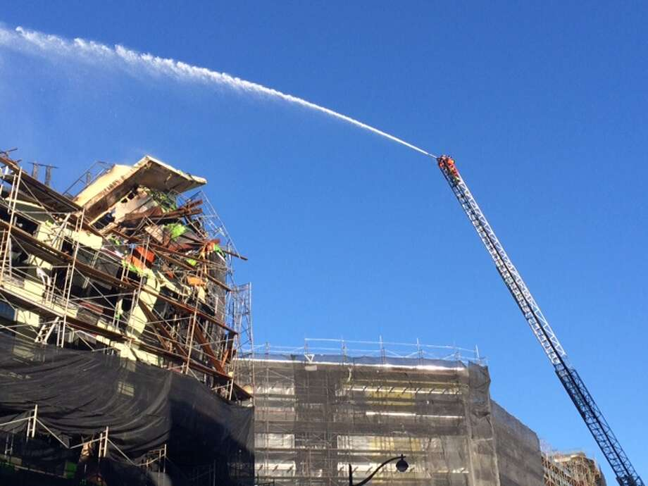Firefighters continue to hose down the unfinished apartment building that caught fire on Tuesday, March 12, 2014 in the Mission Bay area of San Francisco, Calif. Photo: Lea Suzuki, The Chronicle