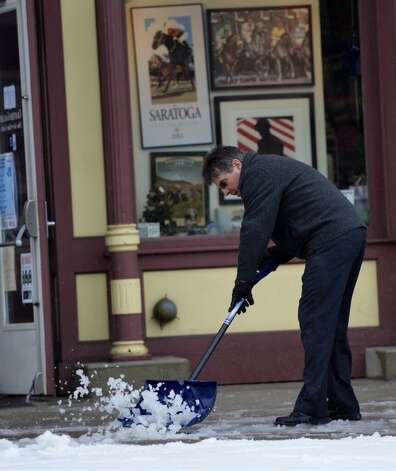 A man shovels snow from the sidewalk in front of Crafters Gallery on Broadway in Saratoga Springs. (Skip Dickstein/Times Union)