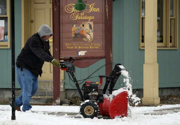 A man clears snow along Circular Street and Broadway in Saratoga Springs. (Skip Dickstein/Times Union)