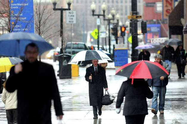 Pedestrians shield themselves from the rain on North Pearl Street on Wednesday, March 12, 2014, in Albany, N.Y. (Cindy Schultz / Times Union) Photo: Cindy Schultz / 00026108A