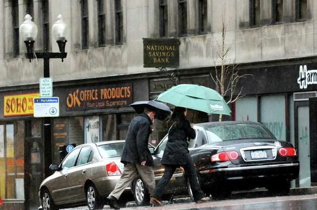 Pedestrians shield themselves from the wind and rain as they cross North Pearl Street on Wednesday, March 12, 2014, in Albany, N.Y. (Cindy Schultz / Times Union) Photo: Cindy Schultz / 00026108A