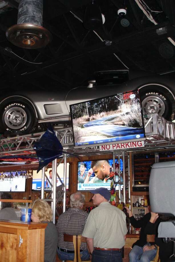 At Stingrays Taphouse and Grill in Port Aransas, customers enjoy some drinks while sitting below two 1970s-era Corvette Stingrays. The restaurant is named for the car and the fish. Photo: Audrey Lee, San Antonio Express-News