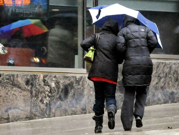 Pedestrians shield themselves from the wind and rain on State Street on Wednesday, March 12, 2014, in Albany, N.Y. (Cindy Schultz / Times Union) Photo: Cindy Schultz / 00026108A