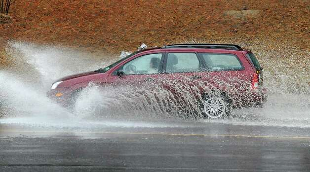 A car makes a big splash as it goes through a partially flooded area on Fuller Rd. on Wednesday, March 12, 2014, in Albany, N.Y.  (Lori Van Buren / Times Union) Photo: Lori Van Buren / 00026108A