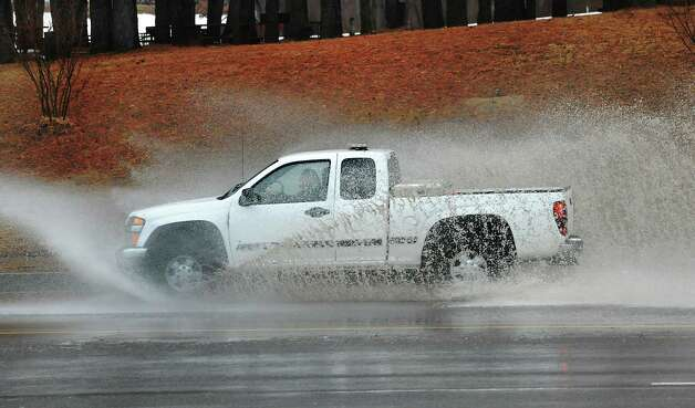 A pickup truck makes a big splash as it goes through a partially flooded area on Fuller Rd. on Wednesday, March 12, 2014, in Albany, N.Y.  (Lori Van Buren / Times Union) Photo: Lori Van Buren / 00026108A