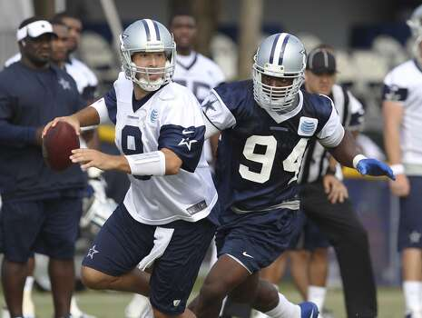 Quarterback Tony Romo (left) attempts to run away from defensive end DeMarcus Ware (94) during the afternoon session of the 2013 Dallas Cowboys training camp on Monday, July 22, 2013 in Oxnard. Photo: Kin Man Hui, San Antonio Express-News