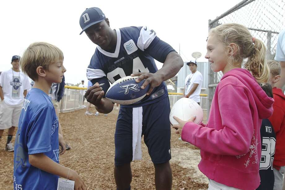 Young fans Skyler Ohlmeyer (right) and Brandon Gorski get an autograph from Dallas Cowboys defensive end DeMarcus Ware (94) at the Cowboys training camp on Sunday, July 21, 2013 in Oxnard. Photo: Kin Man Hui, San Antonio Express-News