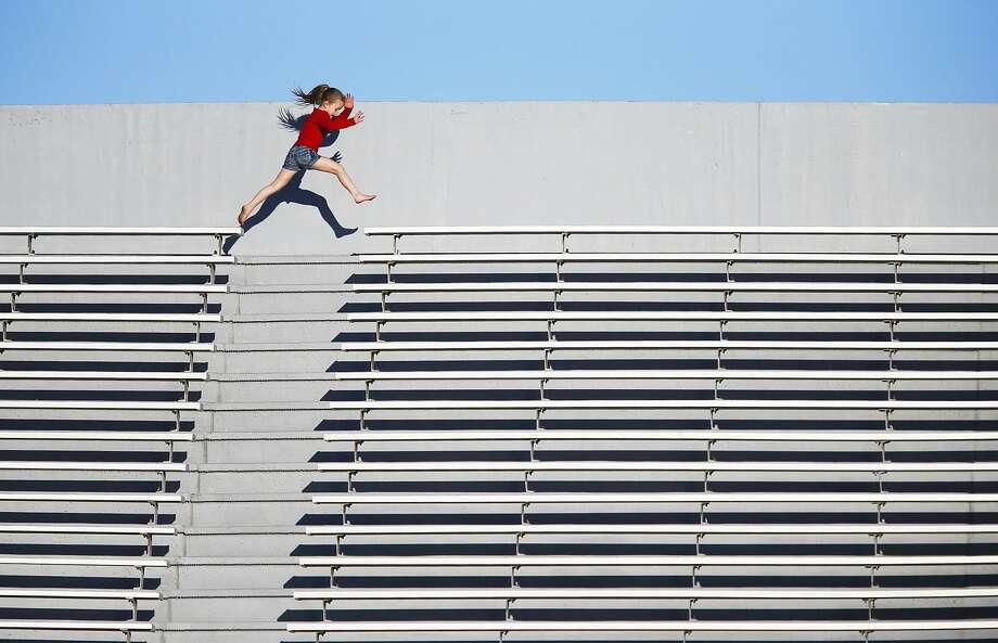 Bleacher hopper:When a soccer game gets boring, 7-year-old Mekenzie Blanchard runs the stadium seats at Booker T. Washington High School in Tulsa. Photo: Tom Gilbert, Associated Press