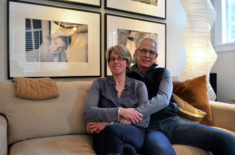 Trudie and Ben Larrabee embrace in their Darien home. The front room of their home serves as their studio space. Photo: Megan Spicer / Darien News