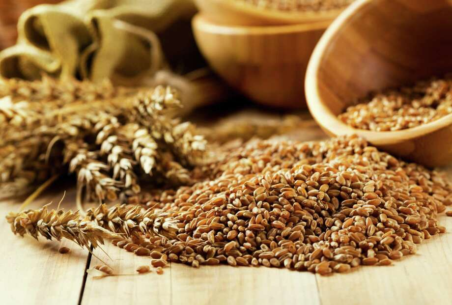 bowl of wheat grains on wooden table / Nitr - Fotolia