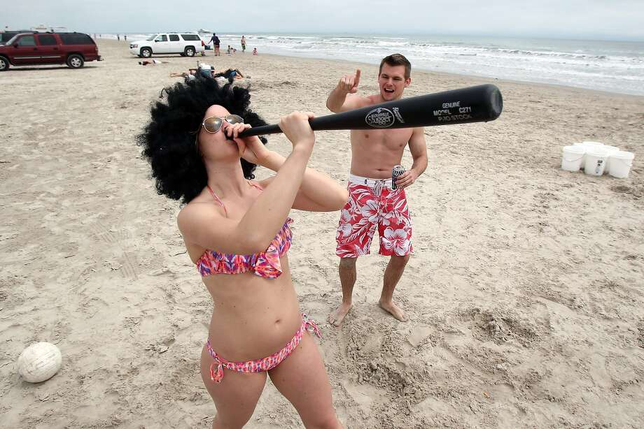 A Louisville chugger, no doubt: Chris Thomas counts off seconds as Lauren Sparrow, a student at the University of Texas Health Science Center in San Antonio, drinks an alcoholic beverage from a hollow plastic baseball bat before spinning around and swinging at a pitch during Spring Break in Port Aransas, Texas. Photo: Michael Zamora, Associated Press