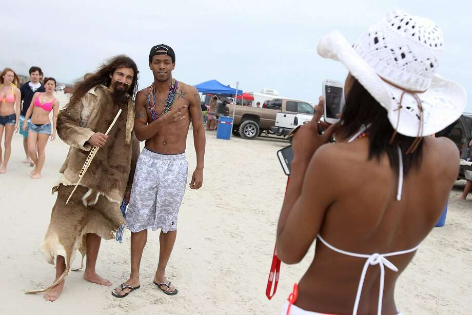 Even troglodytes go to spring break:Denzell Boone gets his picture taken with Nathan Martinez, who roams the beach in Port Aransas, Texas, wearing four deerskins and a bone in his nose. . Photo: Michael Zamora, Associated Press