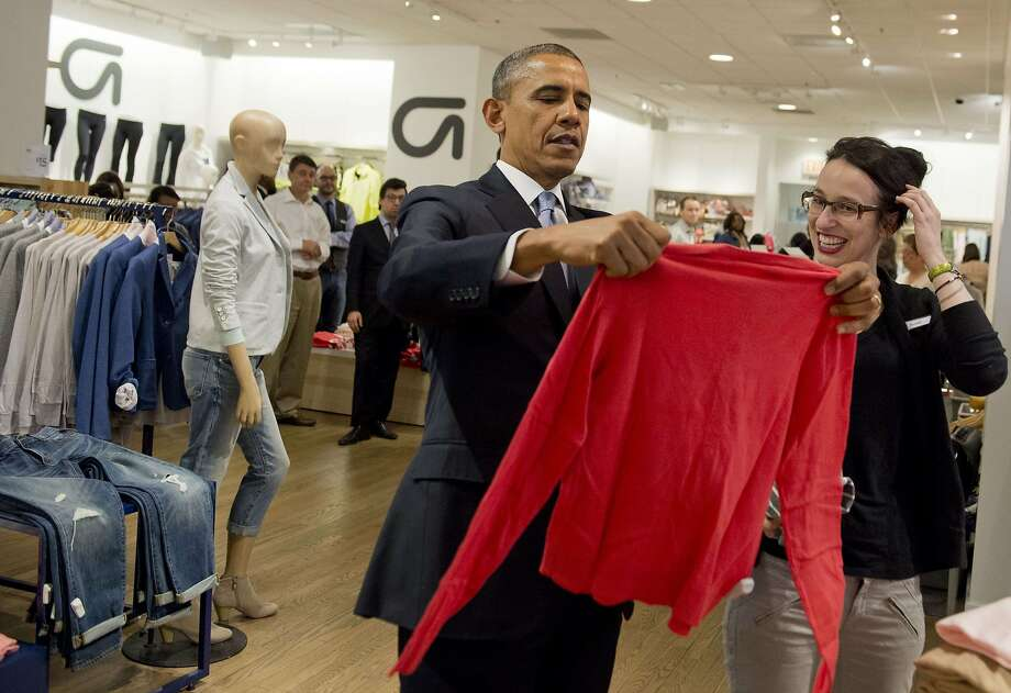 I trust you have a liberal return policy? President Obama holds up a shirt as he shops for clothing for his family alongside store employee Susan Panariello at a Gap in New York City. The president's trip was intended to highlight his proposal to raise the federal minimum wage. Photo: Saul Loeb, AFP/Getty Images