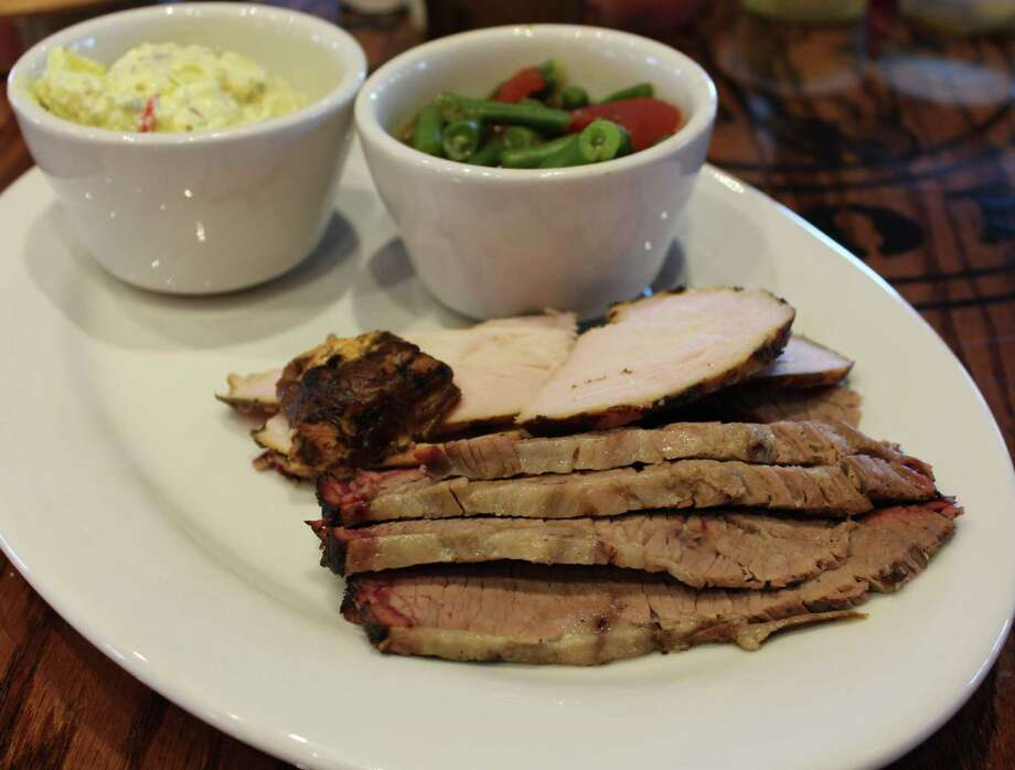 Above, a plate of brisket, turkey, stewed tomatoes and green beans and Cajun potato salad at Choke Canyon Bar-B-Q. Photo: Jennifer McInnis / San Antonio Express-News