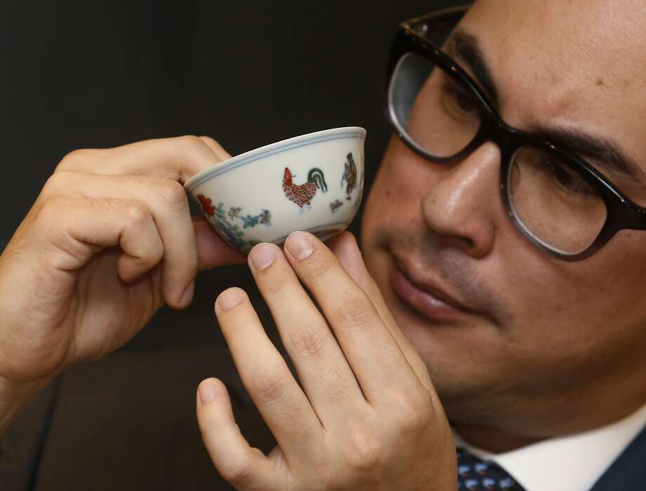"Probably not dishwasher-safe: A staff member from Sotheby's presents the Meiyintang ""Chicken Cup"" from the Chinese Ming Dynasty (1368-1644) during the media preview for the auction of Fine Art Chinese Ceramics and Works of Art in Hong Kong. The cup is expected to fetch between $25.6 million and $38.5 million. Photo: Kin Cheung, Associated Press"