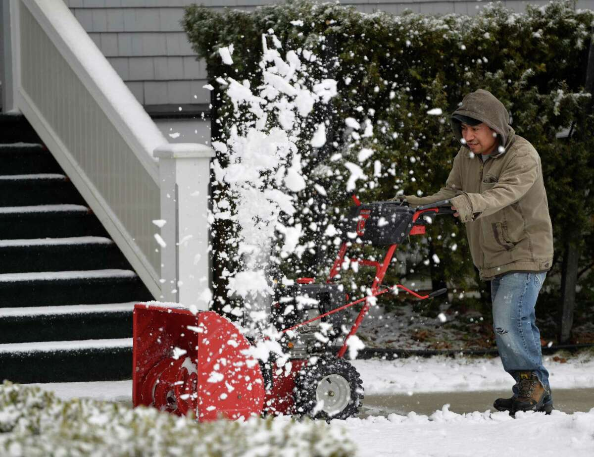 Simon Lopez removes slush from the sidewalk on upper Broadway Wednesday afternoon, March 12, 2014, as a late winter storm hits Saratoga Springs, N.Y. (Skip Dickstein / Times Union)