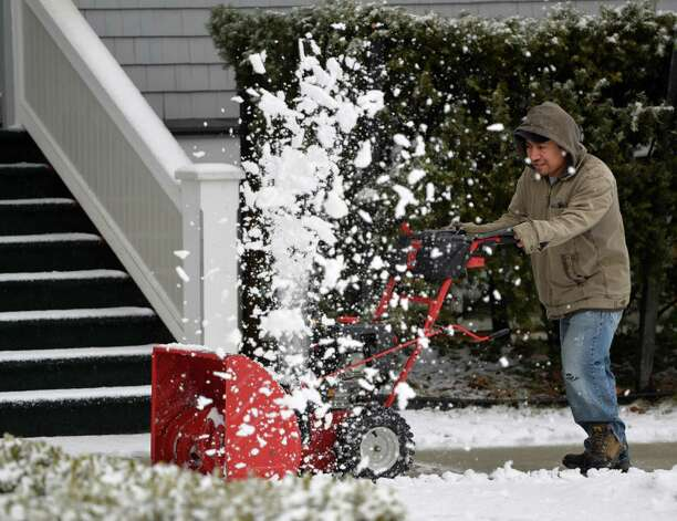 Simon Lopez removes slush from the sidewalk on upper Broadway Wednesday afternoon, March 12, 2014, as a late winter storm hits Saratoga Springs, N.Y. (Skip Dickstein / Times Union) Photo: SKIP DICKSTEIN / 00026108A