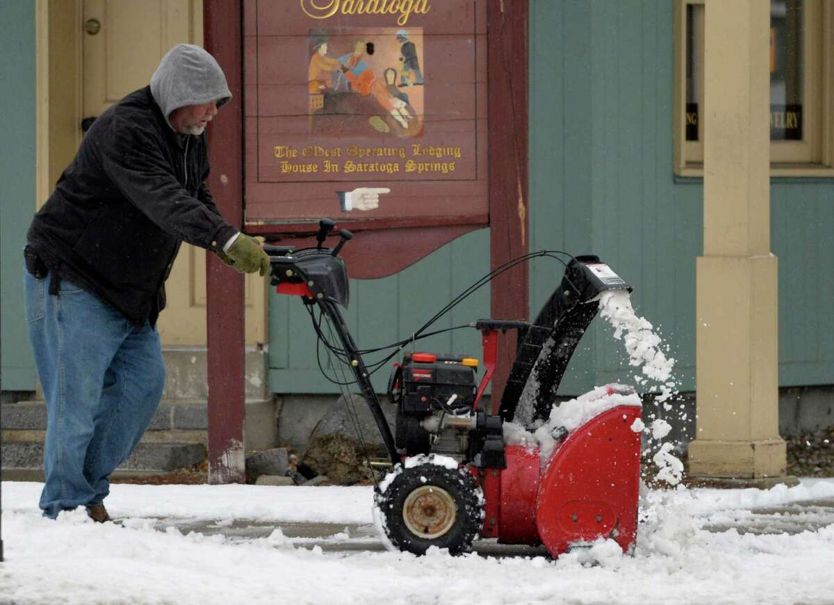 A worker removes slush from the sidewalk at the corner of West. Circular and Broadway Wednesday afternoon, March 12, 2014, as a late winter storm hits Saratoga Springs, N.Y. (Skip Dickstein / Times Union)